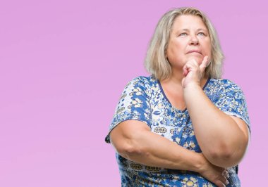 Senior plus size caucasian woman over isolated background with hand on chin thinking about question, pensive expression. Smiling with thoughtful face. Doubt concept.