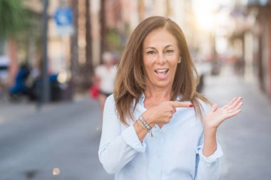 Beautiful middle age hispanic woman at the city street on a sunny day very happy pointing with hand and finger