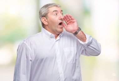 Handsome senior man over isolated background shouting and screaming loud to side with hand on mouth. Communication concept.