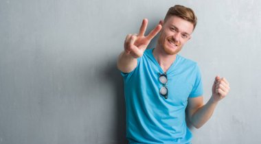 Young redhead man over grey grunge wall wearing casual outfit smiling looking to the camera showing fingers doing victory sign. Number two.