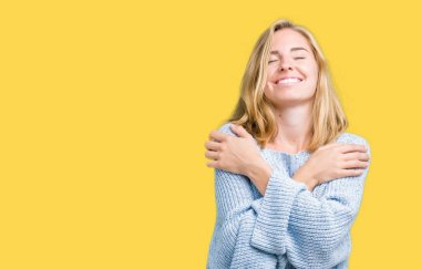 Beautiful young woman wearing blue sweater over isolated background Hugging oneself happy and positive, smiling confident. Self love and self care