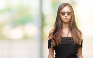 Young asian woman wearing sunglasses over isolated background with serious expression on face. Simple and natural looking at the camera.