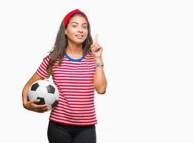 Young beautiful arab woman holding soccer football ball over isolated background surprised with an idea or question pointing finger with happy face, number one