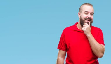 Young caucasian hipster man wearing red shirt over isolated background looking confident at the camera with smile with crossed arms and hand raised on chin. Thinking positive.
