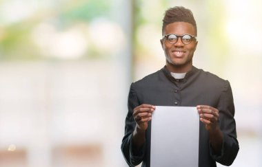 Young african american priest man over isolated background holding blank paper with a happy face standing and smiling with a confident smile showing teeth