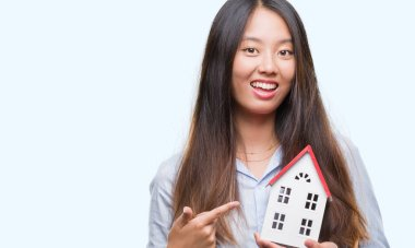 Young asian woman real state agent holding house isolated background very happy pointing with hand and finger