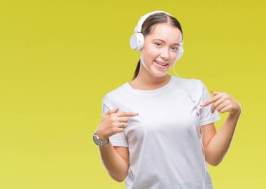 Young caucasian woman listening to music wearing headphones over isolated background looking confident with smile on face, pointing oneself with fingers proud and happy.