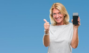 Middle age blonde woman showing blank screen of smartphone over isolated background happy with big smile doing ok sign, thumb up with fingers, excellent sign