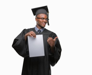 Young graduated african american man holding blank paper degree over isolated background pointing and showing with thumb up to the side with happy face smiling