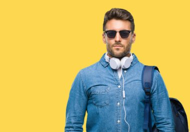Young handsome tourist man wearing headphones and backpack over isolated background with serious expression on face. Simple and natural looking at the camera.