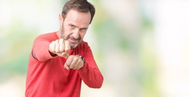 Handsome middle age hoary senior man wearing winter sweater over isolated background Punching fist to fight, aggressive and angry attack, threat and violence