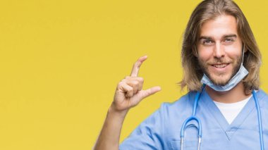 Young handsome doctor man with long hair over isolated background smiling and confident gesturing with hand doing size sign with fingers while looking and the camera. Measure concept.