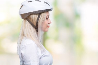 Young blonde woman wearing cyclist security helmet over isolated background looking to side, relax profile pose with natural face with confident smile.