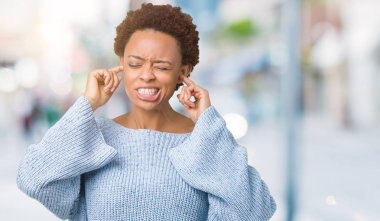 Young beautiful african american woman wearing a sweater over isolated background covering ears with fingers with annoyed expression for the noise of loud music. Deaf concept.