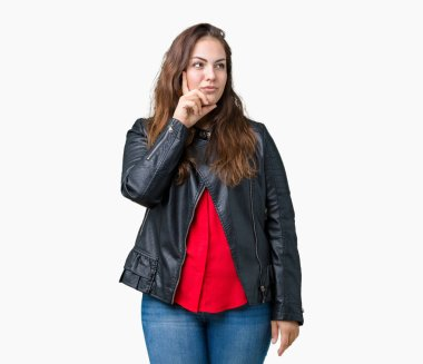 Beautiful plus size young woman wearing a fashion leather jacket over isolated background with hand on chin thinking about question, pensive expression. Smiling with thoughtful face. Doubt concept.