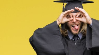 Young handsome graduated man with long hair over isolated background doing ok gesture like binoculars sticking tongue out, eyes looking through fingers. Crazy expression.