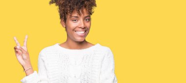 Beautiful young african american woman wearing winter sweater over isolated background smiling with happy face winking at the camera doing victory sign. Number two.