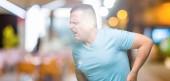 Középkori arab férfi viselt kék póló, felső elszigetelt háttér kézzel a gyomor, mert hányinger, fájdalmas betegség, rossz közérzet. Ache koncepció.