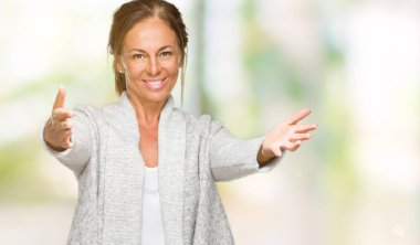 Beautiful middle age adult woman wearing winter sweater over isolated background looking at the camera smiling with open arms for hug. Cheerful expression embracing happiness.