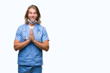 Young handsome doctor man with long hair over isolated background praying with hands together asking for forgiveness smiling confident.