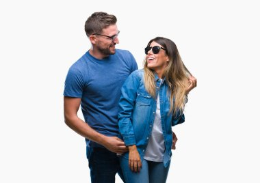 Young couple in love wearing sunglasses over isolated background looking away to side with smile on face, natural expression. Laughing confident.