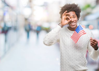 Afro american man flag of United States of America over isolated background with happy face smiling doing ok sign with hand on eye looking through fingers