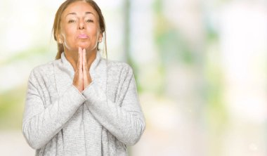 Beautiful middle age adult woman wearing winter sweater over isolated background praying with hands together asking for forgiveness smiling confident.