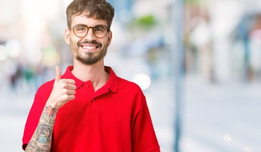 Young handsome man wearing glasses over isolated background doing happy thumbs up gesture with hand. Approving expression looking at the camera showing success.