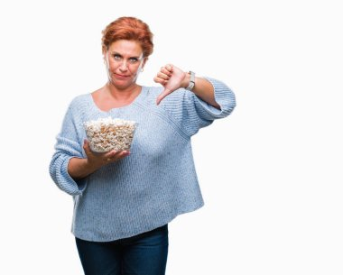 Atrractive senior caucasian redhead woman eating popcorn over isolated background with angry face, negative sign showing dislike with thumbs down, rejection concept