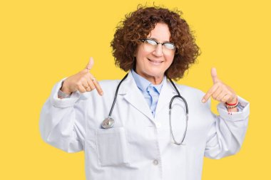 Middle ager senior doctor woman over isolated background looking confident with smile on face, pointing oneself with fingers proud and happy.