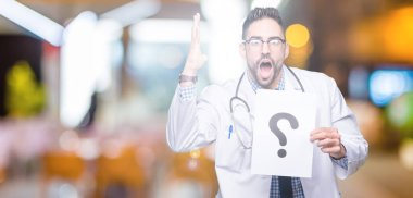 Handsome young doctor man holding paper with question mark over isolated background very happy and excited, winner expression celebrating victory screaming with big smile and raised hands