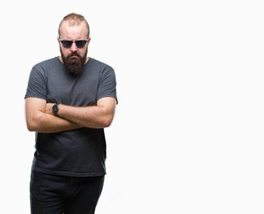 Young caucasian hipster man wearing sunglasses over isolated background skeptic and nervous, disapproving expression on face with crossed arms. Negative person.