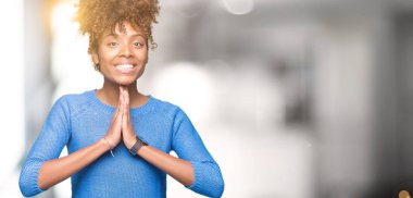 Beautiful young african american woman over isolated background praying with hands together asking for forgiveness smiling confident.