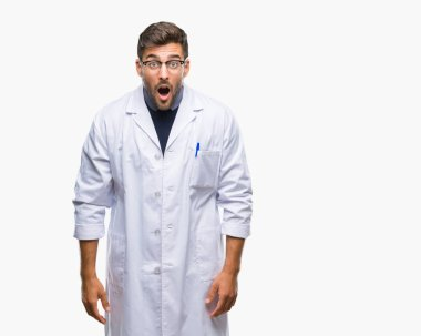 Young handsome man wearing doctor, scientis coat over isolated background afraid and shocked with surprise expression, fear and excited face.