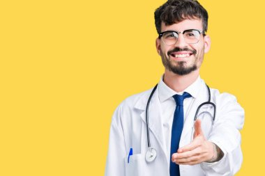 Young doctor man wearing hospital coat over isolated background smiling friendly offering handshake as greeting and welcoming. Successful business.