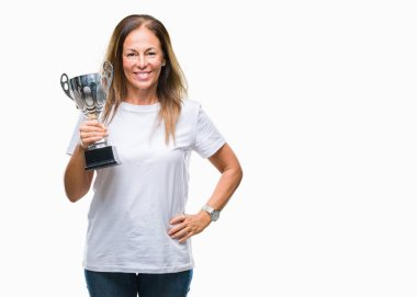 Middle age hispanic winner woman celebrating award holding trophy over isolated background with a happy face standing and smiling with a confident smile showing teeth