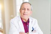 Vedoucí lékař muž na klinice lékařské kabátě a s úsměvem s překřížením rukou