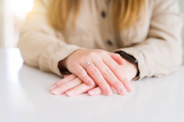 Close up of woman finger showing engagement ring with hands on each other over white table