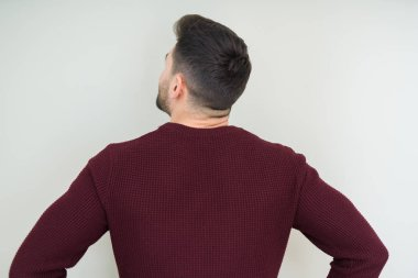 Young handsome man wearing a sweater over isolated background standing backwards looking away with arms on body