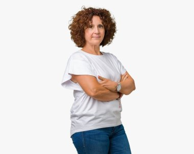 Beautiful middle ager senior woman wearing white t-shirt over isolated background Relaxed with serious expression on face. Simple and natural with crossed arms
