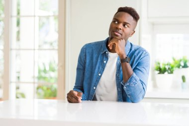 Handsome african american man at home with hand on chin thinking about question, pensive expression. Smiling with thoughtful face. Doubt concept.