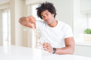 African American man drinking a glass of water at home with angry face, negative sign showing dislike with thumbs down, rejection concept