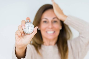 Middle age woman holding stopwatch isolated background stressed with hand on head, shocked with shame and surprise face, angry and frustrated. Fear and upset for mistake.