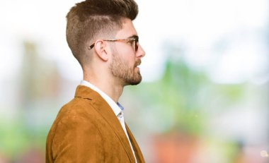 Young handsome business man wearing glasses looking to side, relax profile pose with natural face with confident smile.