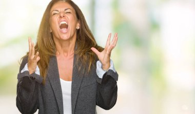 Middle age adult woman wearing oversize boyfriend jacket over isolated background crazy and mad shouting and yelling with aggressive expression and arms raised. Frustration concept.