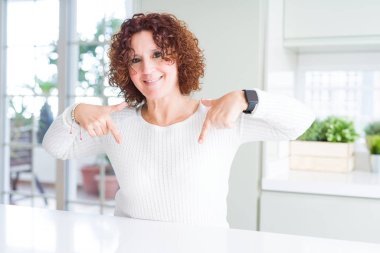 Beautiful senior woman wearing white sweater at home looking confident with smile on face, pointing oneself with fingers proud and happy.