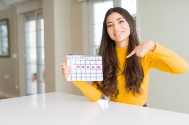 Young woman holding menstruation calendar with surprise face pointing finger to himself