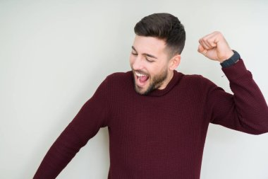 Young handsome man wearing a sweater over isolated background Dancing happy and cheerful, smiling moving casual and confident listening to music
