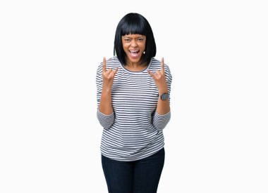 Beautiful young african american woman wearing stripes sweater over isolated background shouting with crazy expression doing rock symbol with hands up. Music star. Heavy concept.