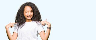 Young beautiful girl with curly hair wearing casual white t-shirt looking confident with smile on face, pointing oneself with fingers proud and happy.